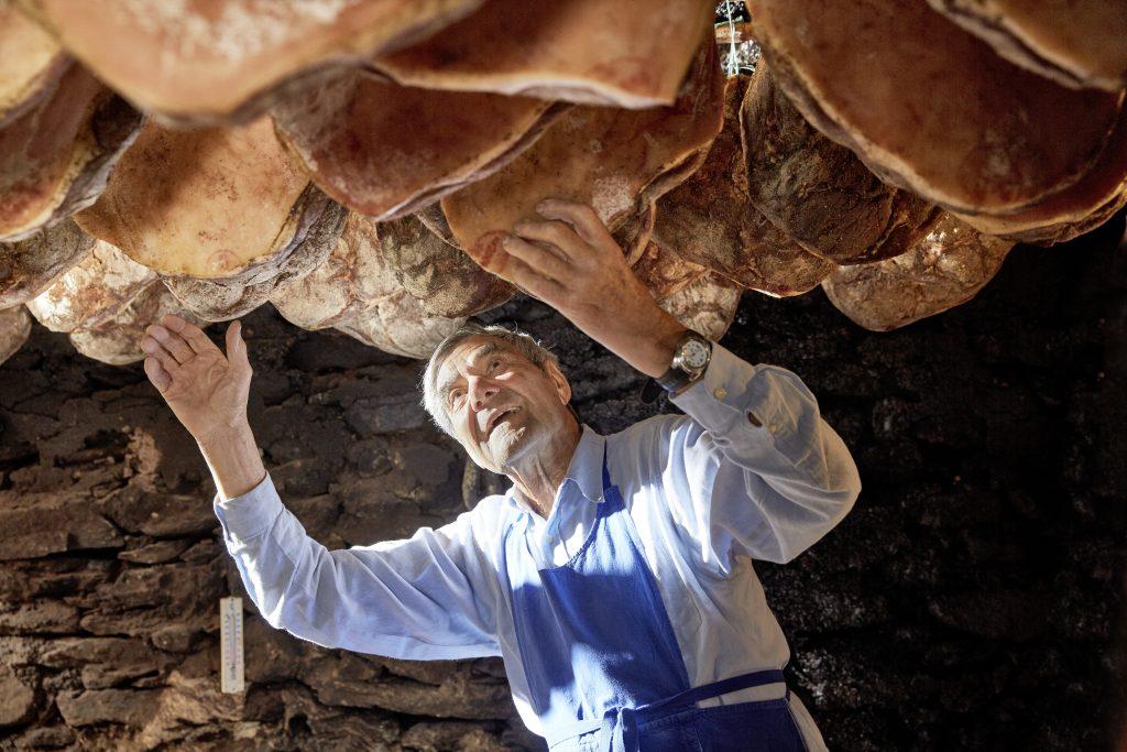 Südtirol Kulinkarik: Senior Chef Josef kontrolliert die Speckseiten an der Kellerdecke